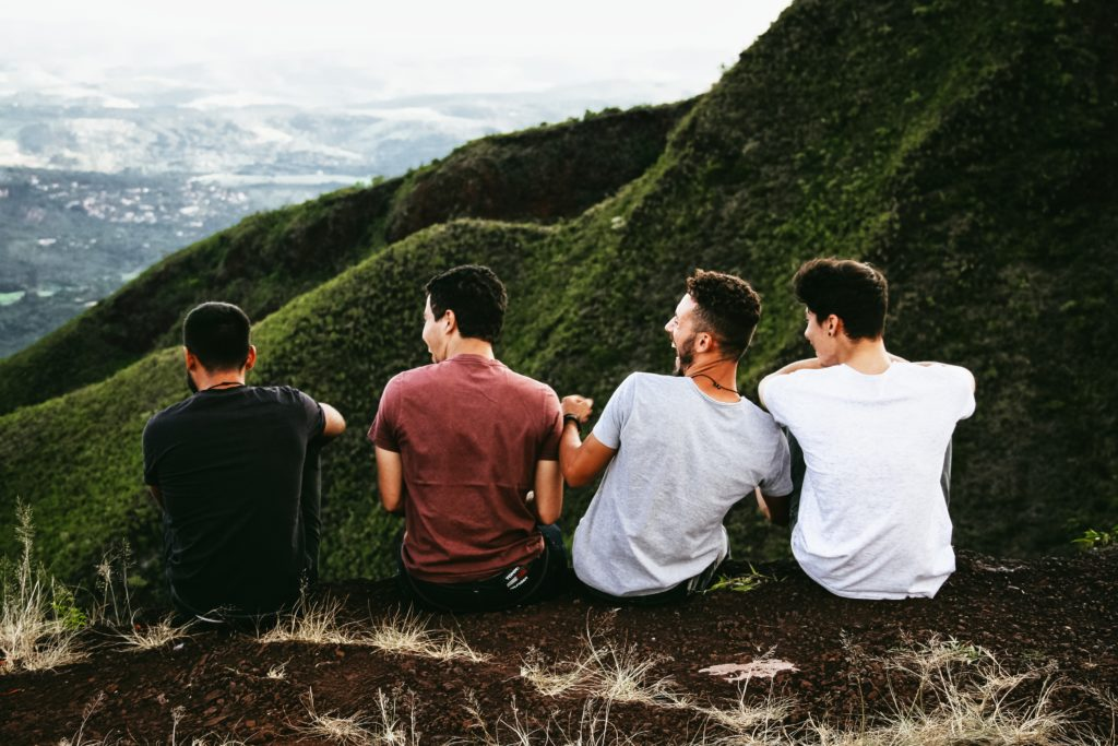 Male friends sitting together on a mountain, laughing.